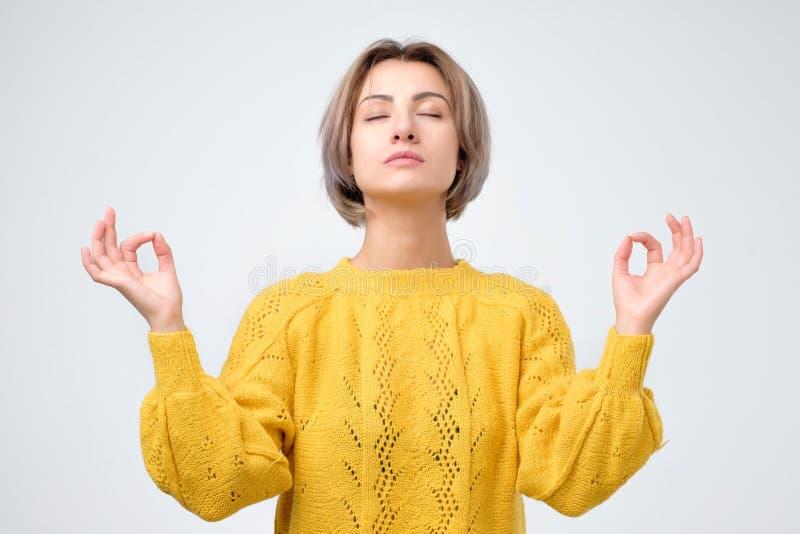 Jeune méditer de sourire de femme, tenant ses mains dans le geste de yoga, se sentant calme images libres de droits