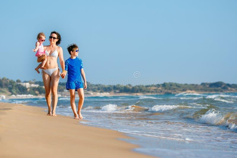 Jeune m?re avec ses deux enfants des vacances tropicales de plage photos libres de droits