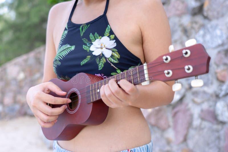 Jeune maillot de bain asiatique d'usage de femme jouant sur l'ukulélé à la plage Concept de saison d'?t? images libres de droits