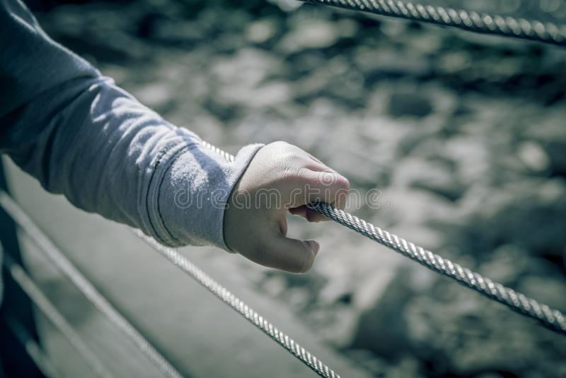 Jeune main de garçon tenant le grillage en métal photos stock