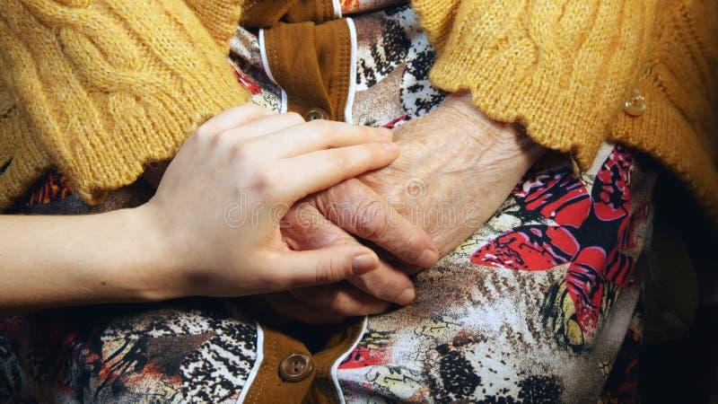 Jeune main soulageant une vieille paire de mains photo libre de droits
