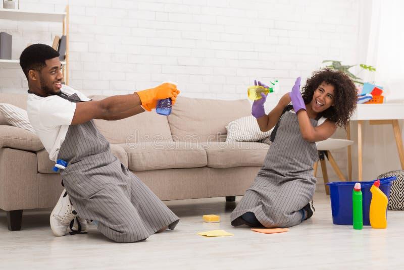 Jeune maison de nettoyage de couples, ayant l'amusement avec des pulvérisateurs photo libre de droits