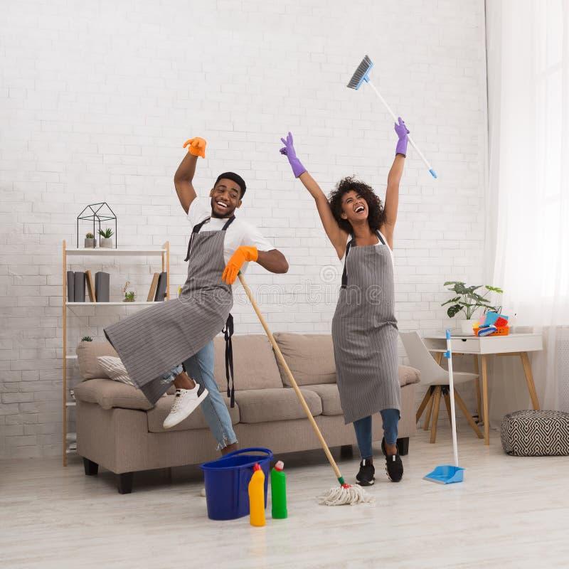 Jeune maison de nettoyage de couples, ayant l'amusement avec le balai et le balai image stock