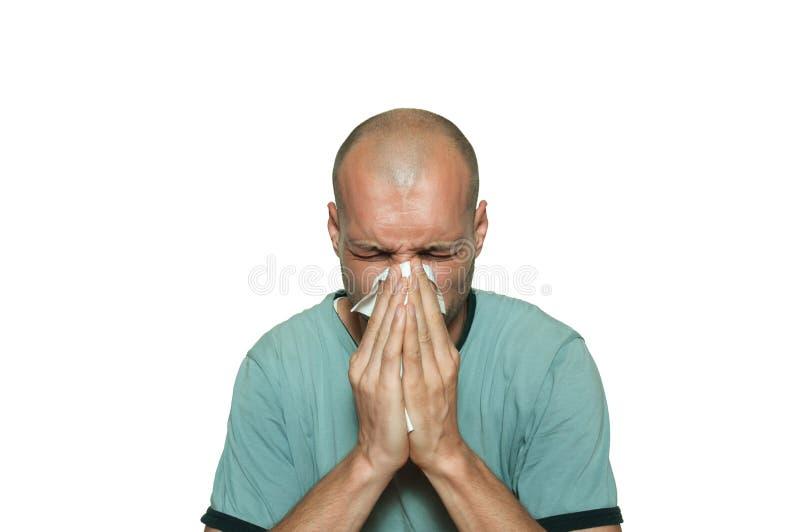 Jeune malade chauve d'homme de la grippe de rhume de cerveau soufflant son nez avec le tissu de papier d'isolement sur le fond bl images stock