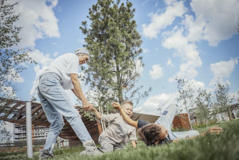 Jeune maman blonde tournant autour, tourbillonnant avec ses fils au parc images stock