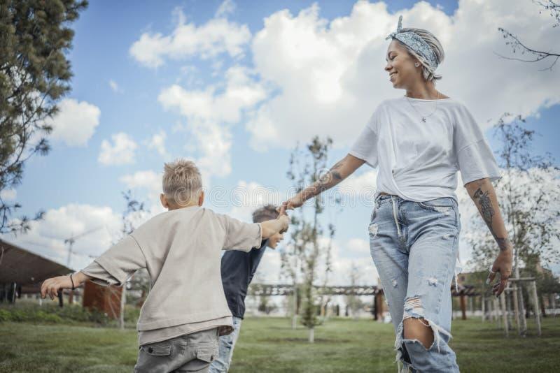 Jeune maman blonde tournant autour, tourbillonnant avec ses fils au parc photo libre de droits