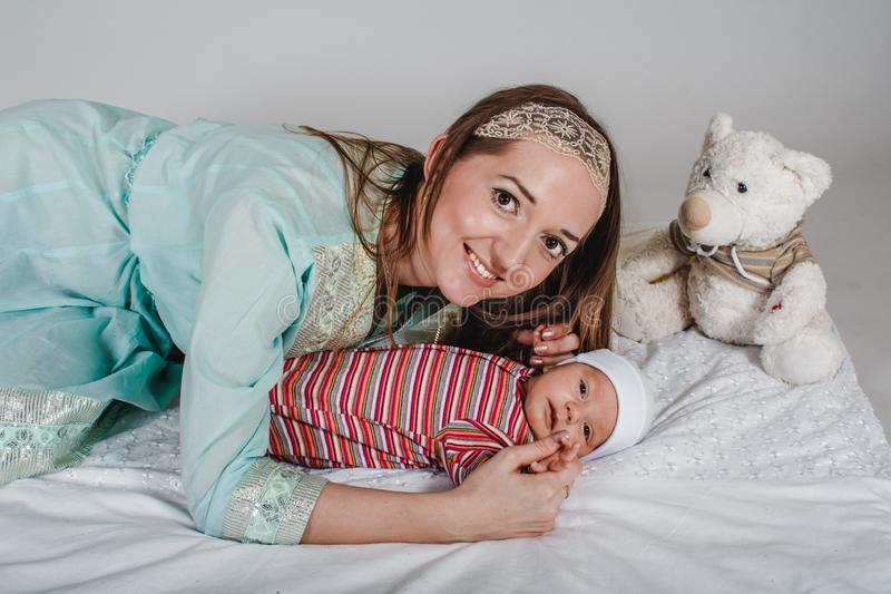 Jeune maman de sourire et enfant en bas ?ge nouveau-n? image stock