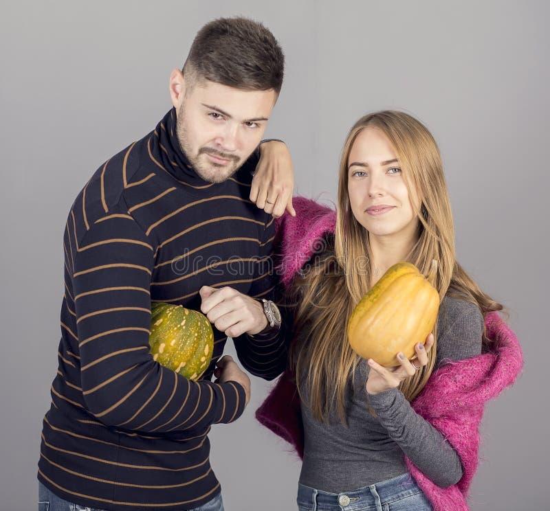 Jeune mand et fille tenant des potirons sur le fond gris images libres de droits
