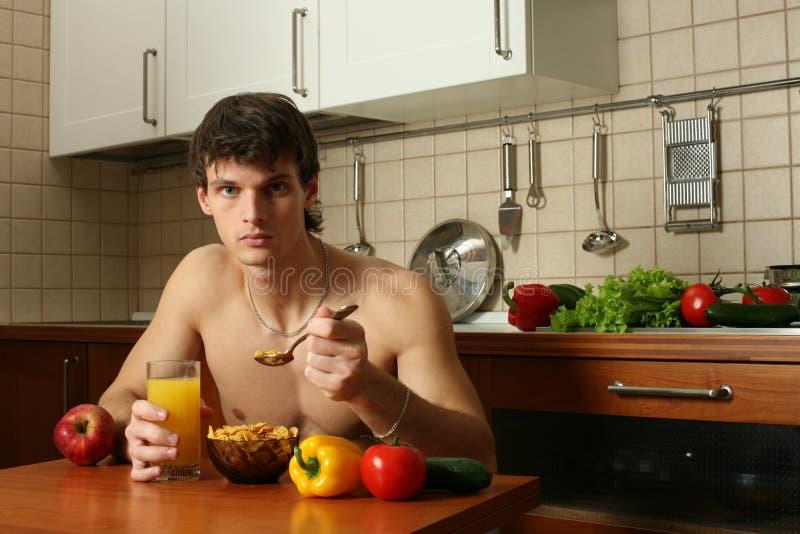 Jeune mangeur d'hommes musculaire son déjeuner photos stock
