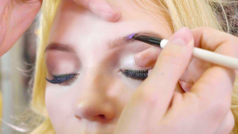 Jeune maquilleur appliquant des cosmétiques sur le visage modèle du ` s photographie stock