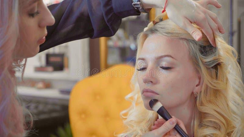 Jeune maquilleur appliquant le crayon correcteur sur le visage modèle du ` s images libres de droits