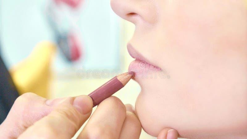 Jeune maquilleur appliquant le rouge à lèvres sur les lèvres modèles du ` s photos stock