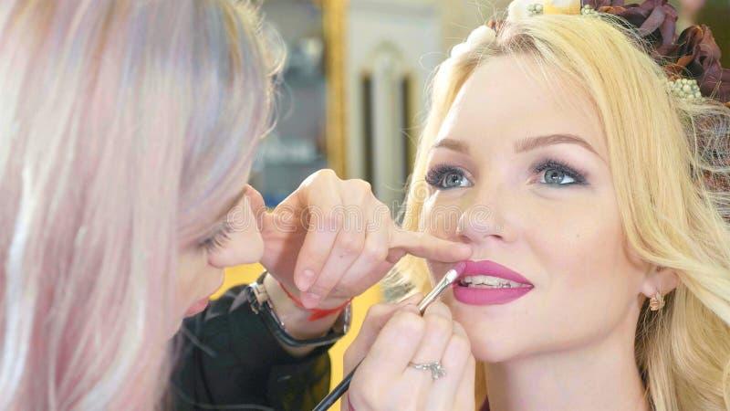Jeune maquilleur appliquant le rouge à lèvres sur les lèvres modèles du ` s photographie stock