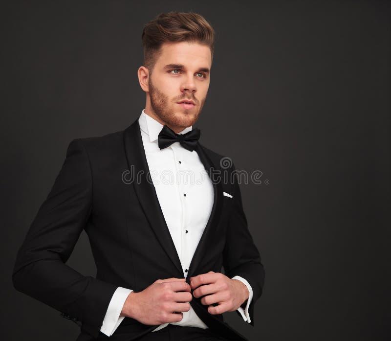 Jeune marié boutonnant son manteau et regardant loin images stock