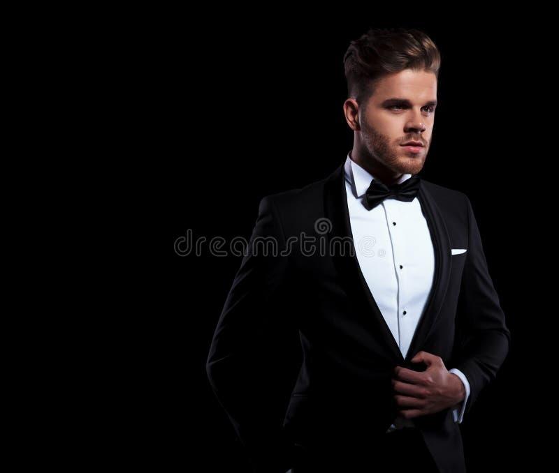 Jeune marié tenant son bouton de manteau images stock