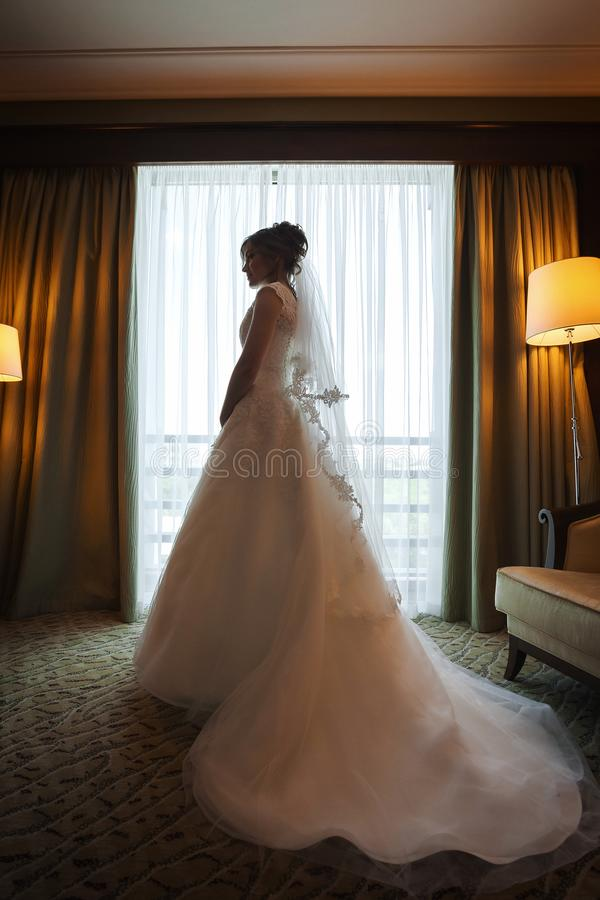 Jeune mariée élégante attirante de brune près d'une fenêtre dans la chambre de luxe image stock