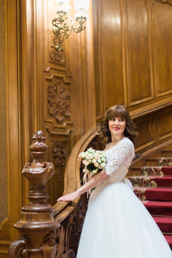 Jeune mariée élégante avec le bouquet tenant la main sur la balustrade à la vieille maison de vintage photos libres de droits
