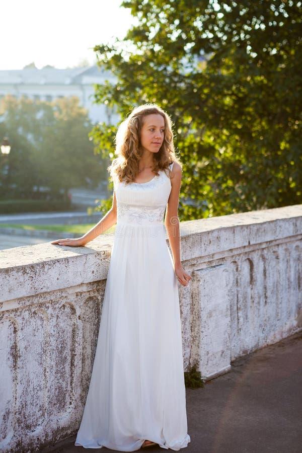 Jeune mariée élégante dans une robe blanche près à la vieille frontière de sécurité concrète blanche photo libre de droits