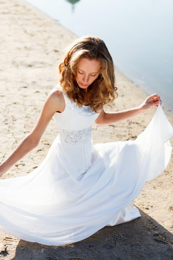 Jeune mariée élégante de jeune fille dans une robe blanche sur une plage arénacée de rivière photos stock