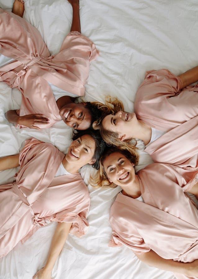 Jeune mariée avec des demoiselles d'honneur se trouvant sur le lit et le sourire photographie stock libre de droits