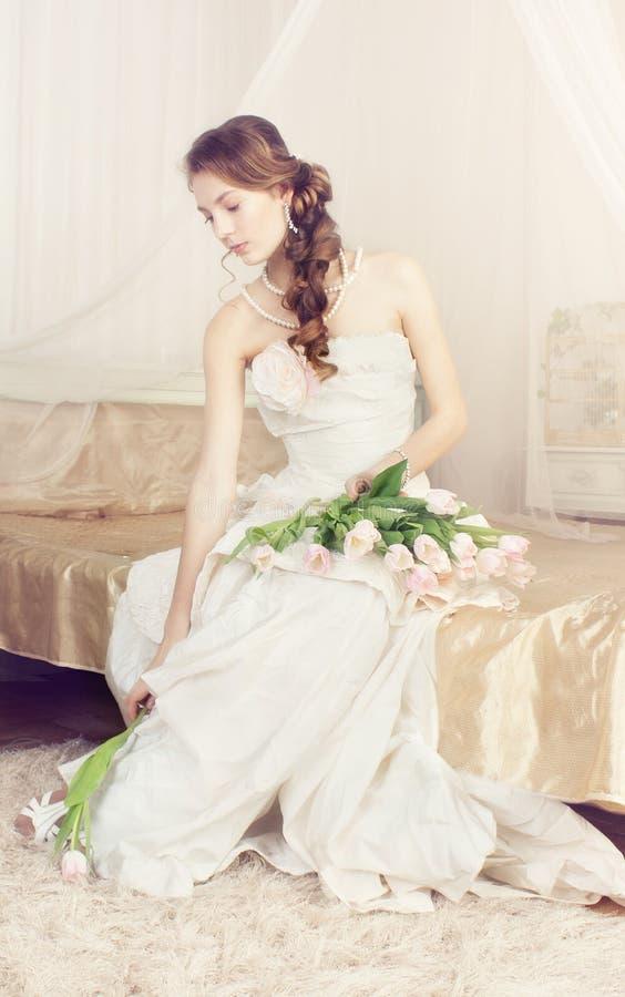 Jeune mariée avec des fleurs dans son boudoir images stock