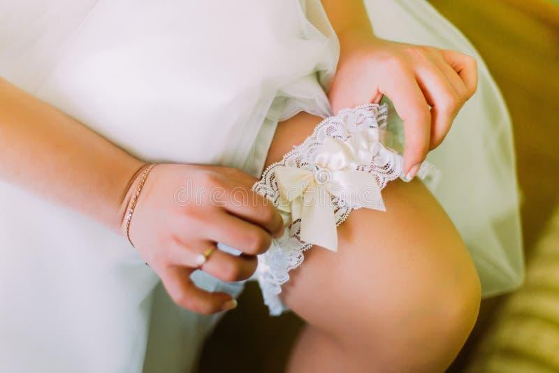 Jeune mariée avec du charme habillant la jarretière nuptiale à l'intérieur Bras en gros plan de femme photo stock