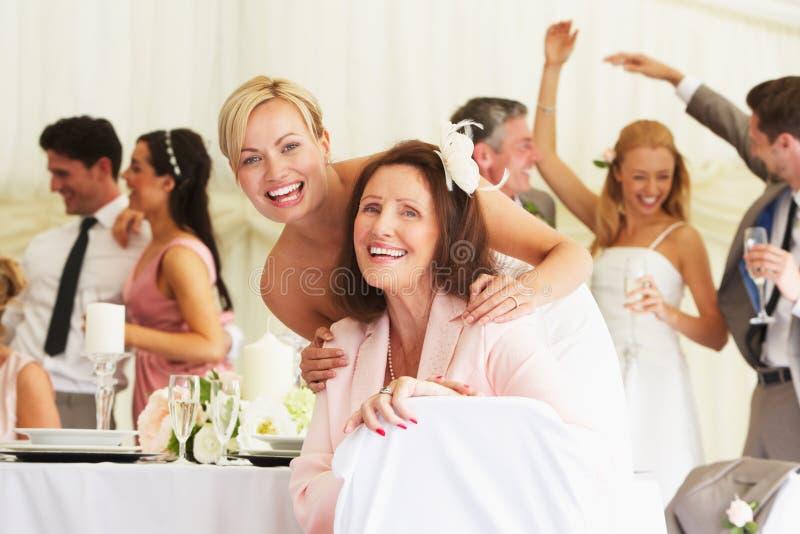 Jeune mariée avec la grand-mère à la réception de mariage photo stock