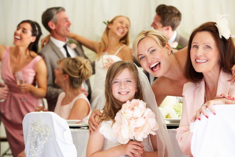 Jeune mariée avec la grand-mère et la demoiselle d'honneur à la réception de mariage photographie stock libre de droits