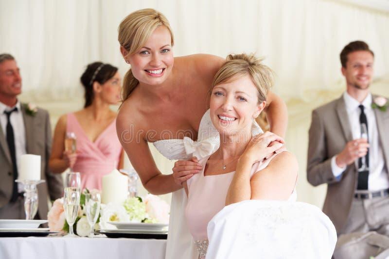 Jeune mariée avec la mère à la réception de mariage photo stock