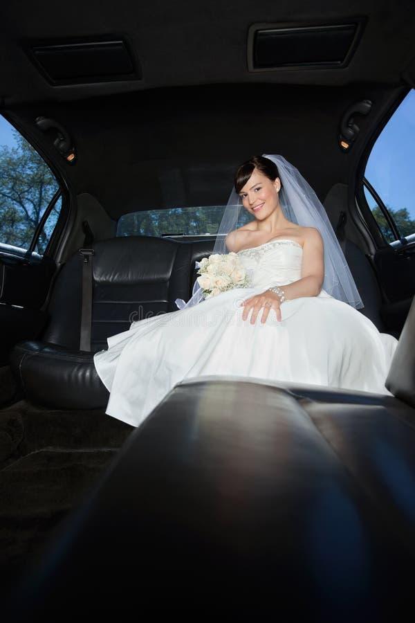 Jeune mariée avec le bouquet de fleur dans la limousine image libre de droits