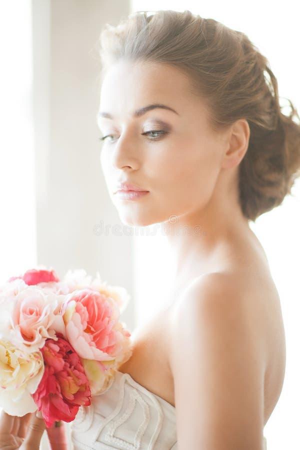 Jeune mariée avec le bouquet des fleurs image libre de droits
