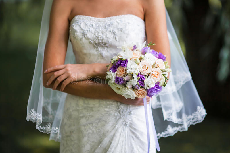 Jeune mariée avec le voile tenant des bouquets de mariage sur la cérémonie de mariage photographie stock