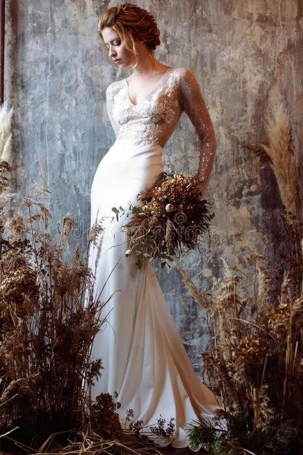 Jeune mariée blonde dans la robe de mariage blanche de mode avec le maquillage photos libres de droits