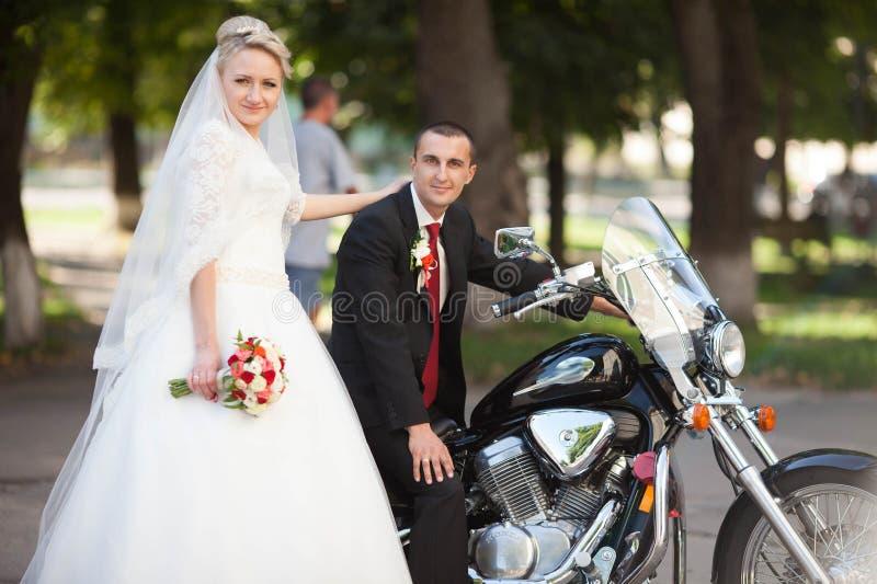 Jeune mariée blonde heureuse se tenant à côté de son aimé qui se repose sur a images stock