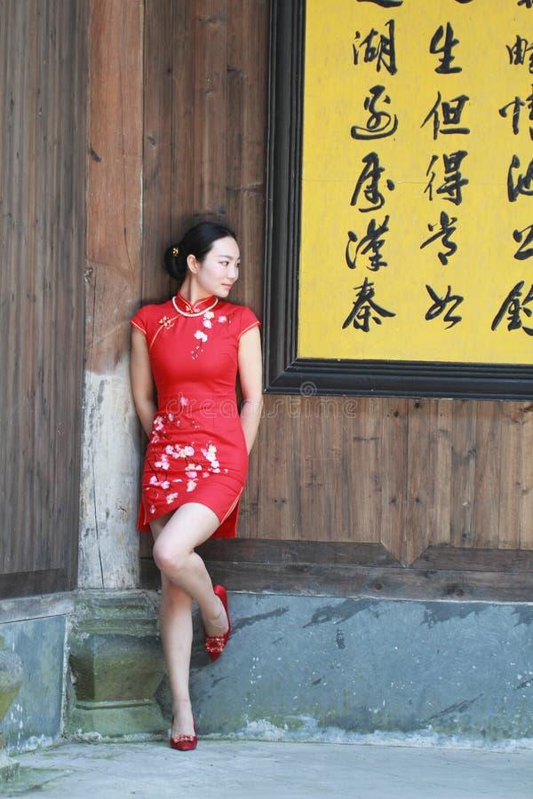 Jeune mariée chinoise heureuse dans le cheongsam rouge au jour du mariage traditionnel images stock