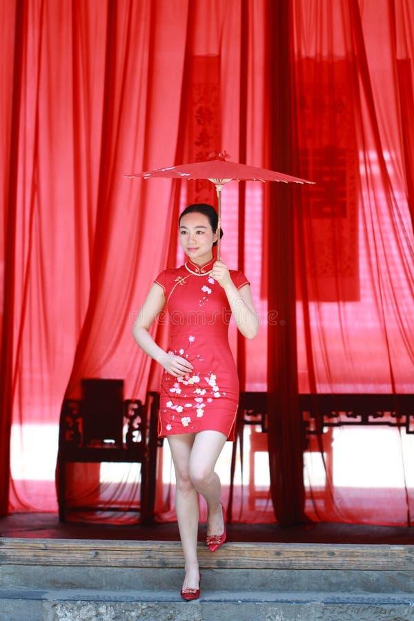 Jeune mariée chinoise heureuse dans le cheongsam rouge au jour du mariage traditionnel photo stock