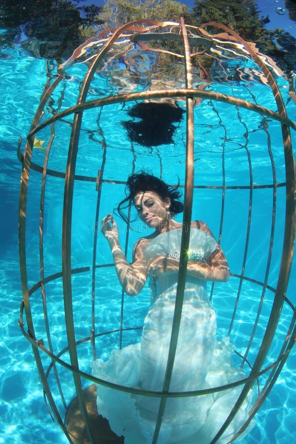 Jeune mariée d'imagination sous-marine dans une cage à oiseaux image libre de droits