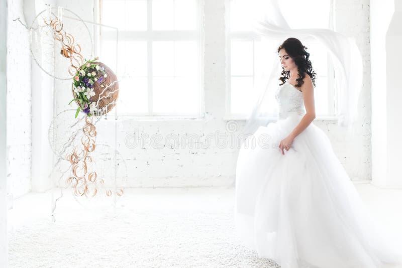Jeune mariée d'une chevelure foncée dans une robe de mariage blanche d'éblouissement photos libres de droits