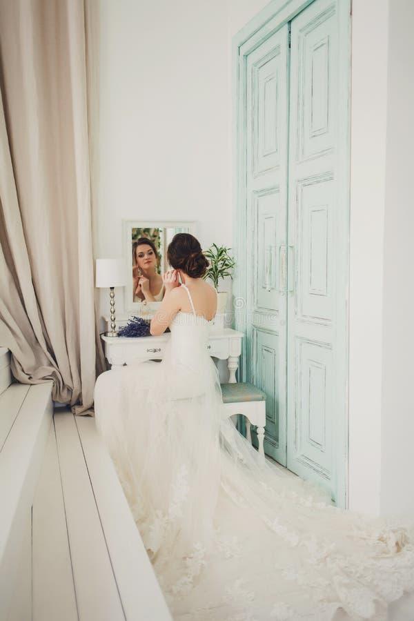 Jeune mariée dans la belle robe se reposant sur la chaise photographie stock
