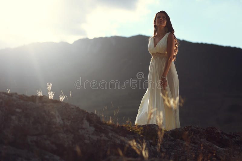 Jeune mariée dans la lumière de coucher du soleil de montagne photos stock