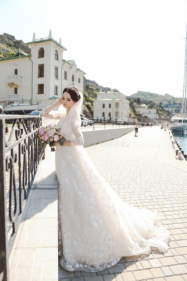 Jeune mariée dans la pose élégante de robe de mariage extérieure avec le bouque tendre photographie stock