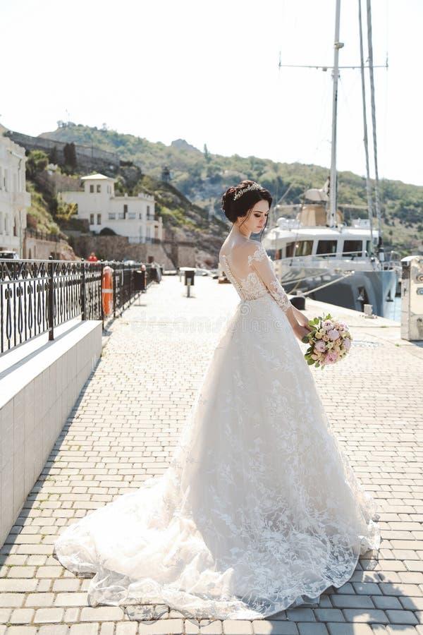 Jeune mariée dans la pose élégante de robe de mariage extérieure avec le bouque tendre image libre de droits