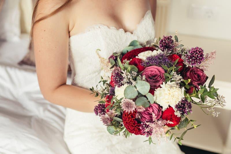 Jeune mariée dans la robe de mariage blanche tenant le bouquet lilas de mariage image stock