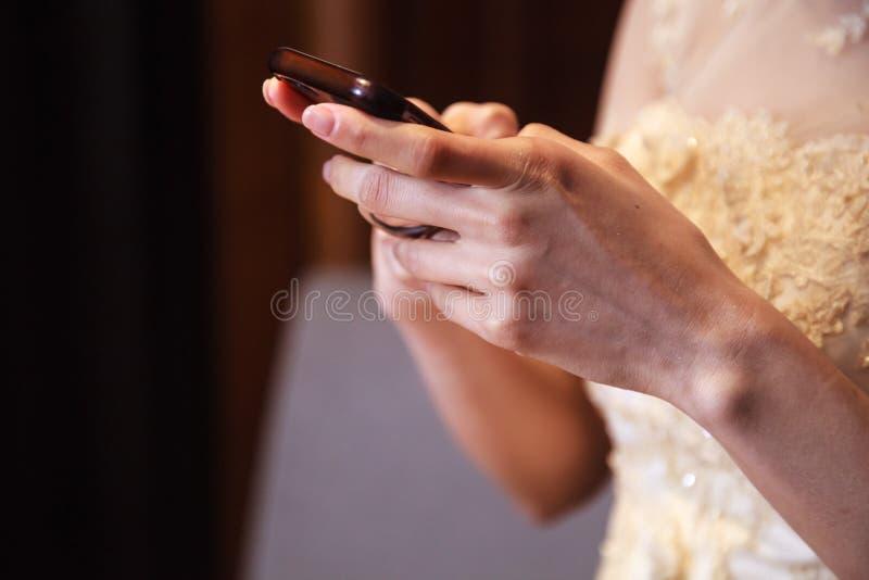 Jeune mariée dans la robe de mariage utilisant le téléphone portable, les achats et la communication futés avec la technologie nu photographie stock