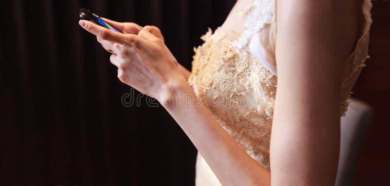 Jeune mariée dans la robe de mariage utilisant le téléphone portable, les achats et la communication futés avec la technologie nu image stock