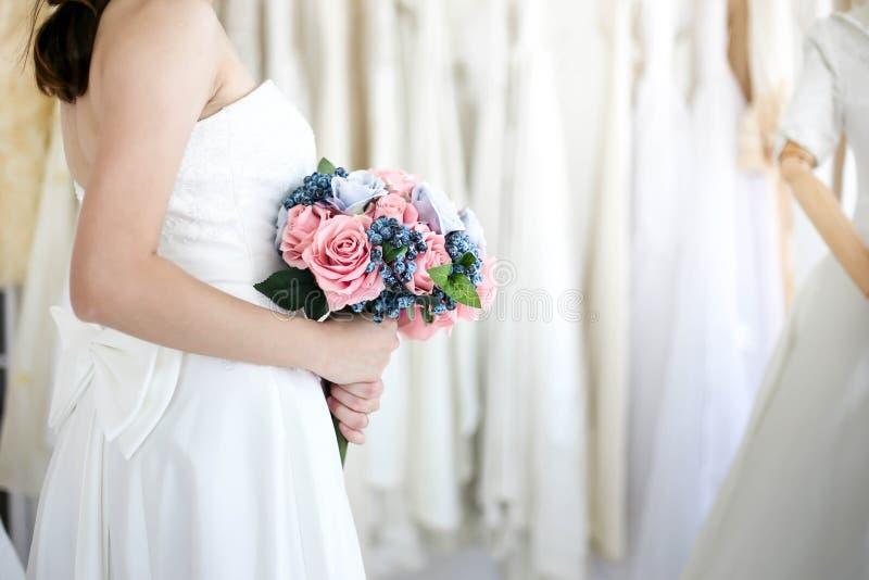 Jeune mariée dans la robe tenant épouser le bouquet des fleurs et de la verdure, concept l'épousant heureux image libre de droits