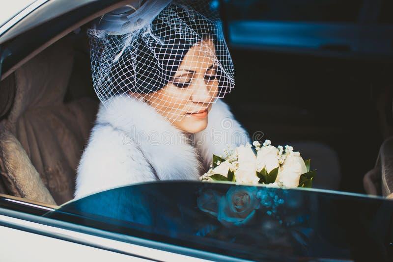 Jeune mariée dans la voiture blanche image stock