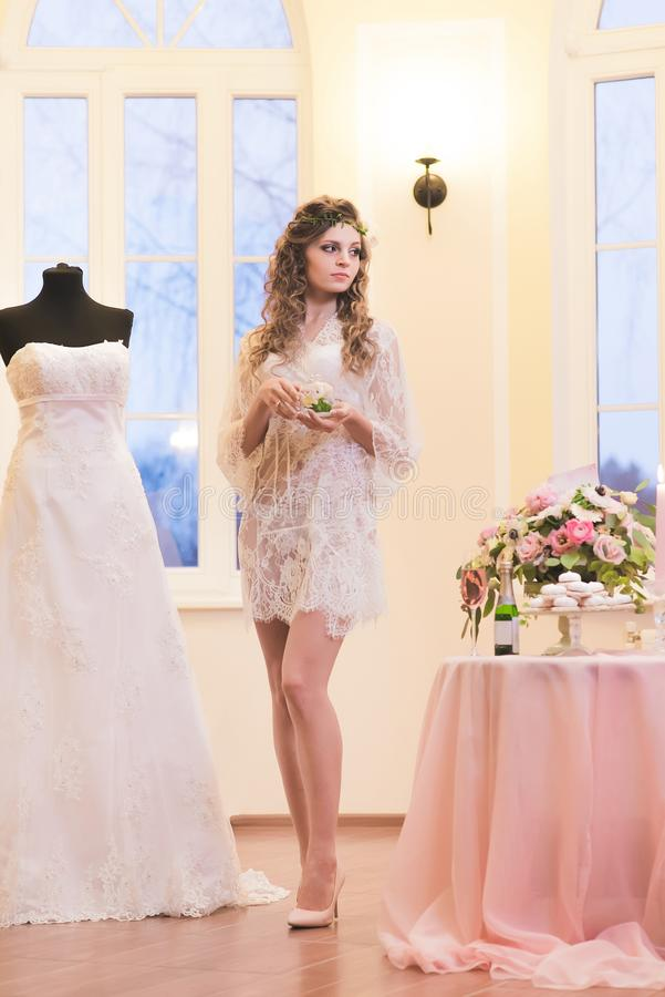 Jeune mariée dans un peignoir se tenant à côté de sa robe de mariage photo libre de droits