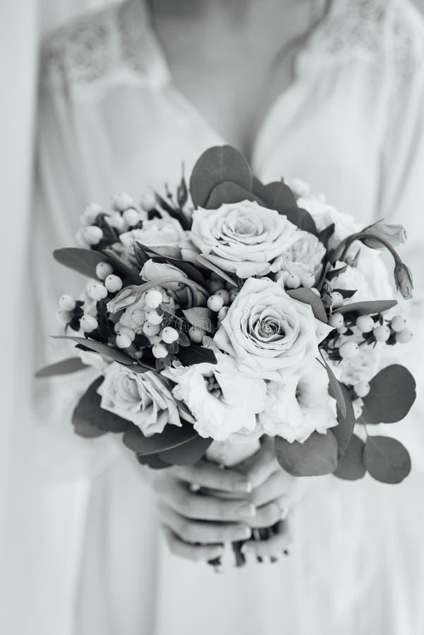 Jeune mariée dans un peignoir tenant son bouquet l'épousant photos stock