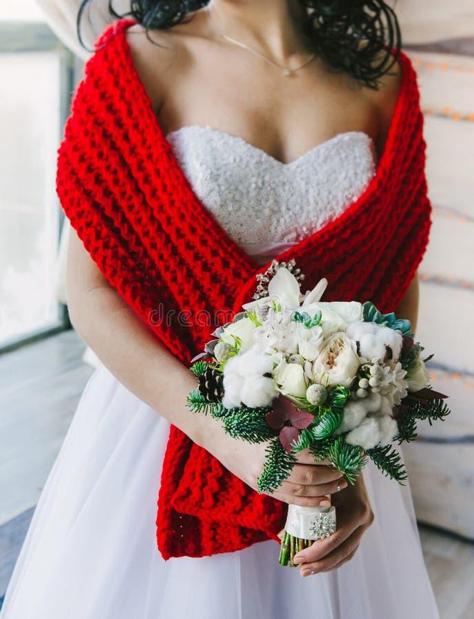 Jeune jeune mariée dans une grande exploitation rouge confortable d'écharpe image libre de droits